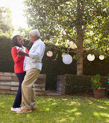 Happy senior couple dancing in sunny backyard