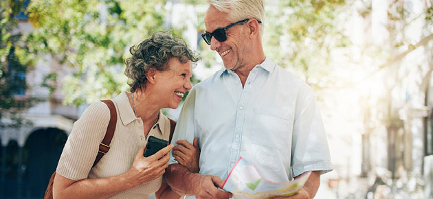 Laughing senior couple outside with map on vacation