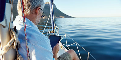 Senior man on sailboat using a tablet