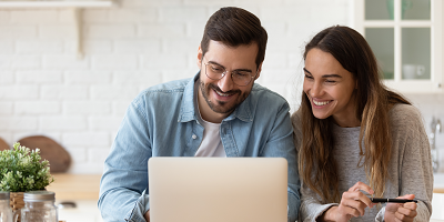 Couple looking at a laptop together, smiling