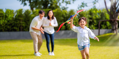 Mom and dad cheering on daughter as she flies a kite