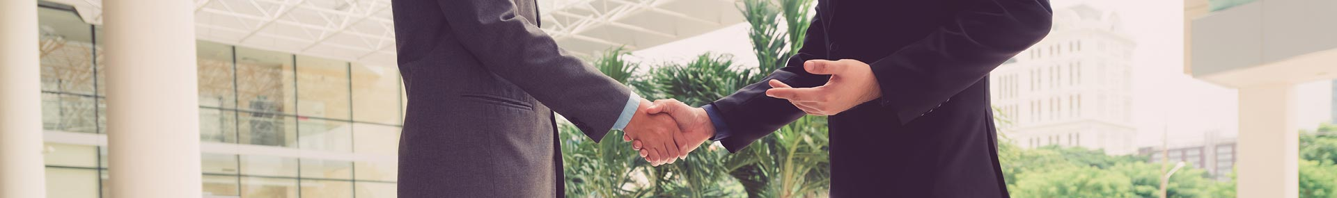 focus of image is on a handshake in an office environment
