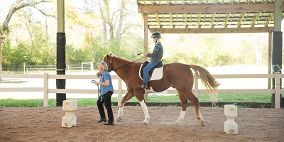 Child riding horse with Special Equestrians program