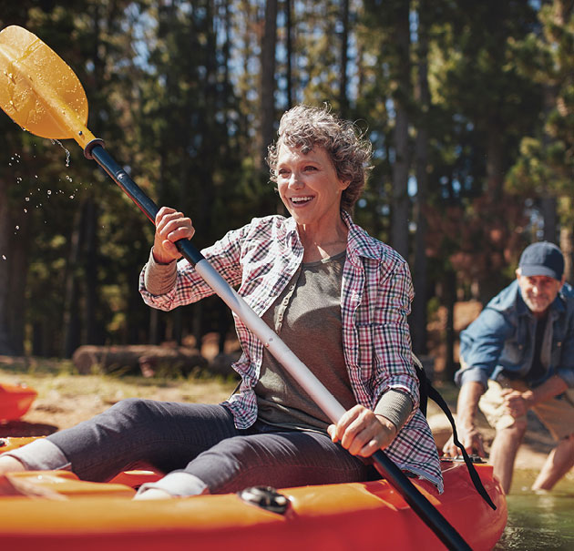 Happy woman shoves off on a kayak