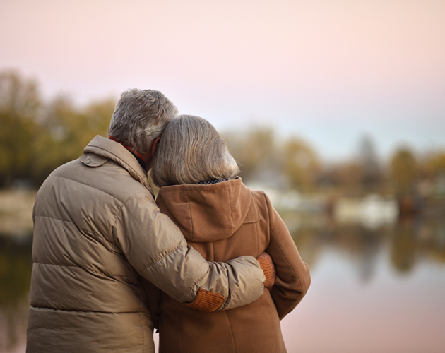 An older man wraps his arm around his wife while they look out over a lake.