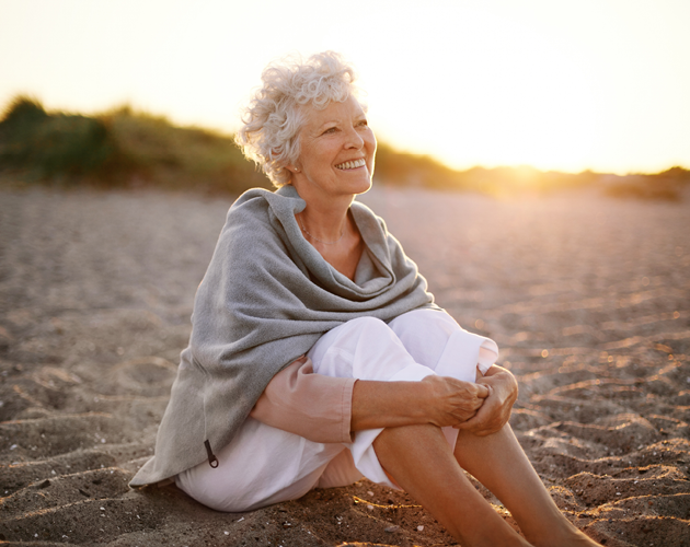 A senior woman sits on the beach at sunset