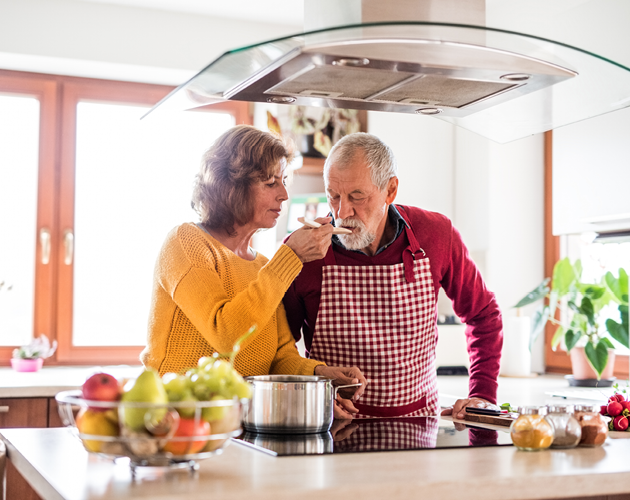 A senior couple cooks together in their kitchen