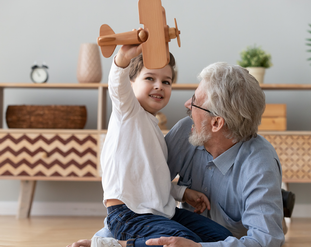 A grandfather plays with his grandson who is holding a wooden airplane toy