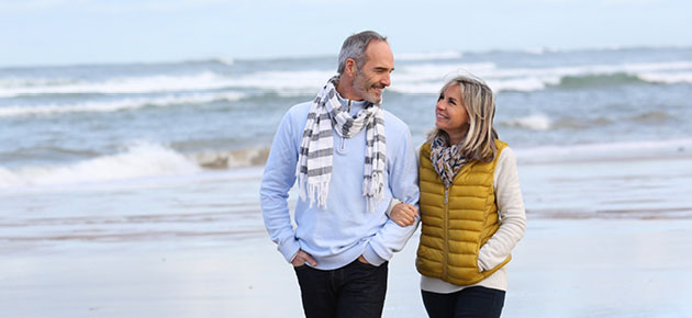 A middle age couple walks together on the beach