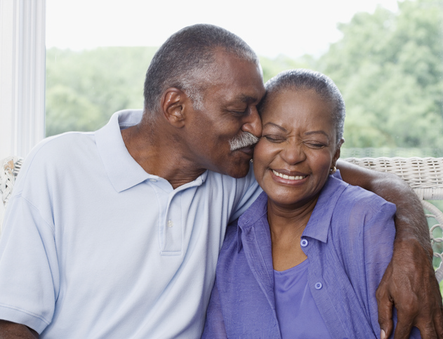 Older african-american couple snuggling on couch