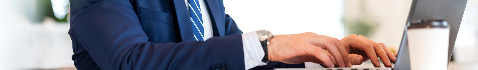 A man dressed in business attire searching on a computer for information.