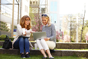Two women business partners meeting outside both working from a shared laptop