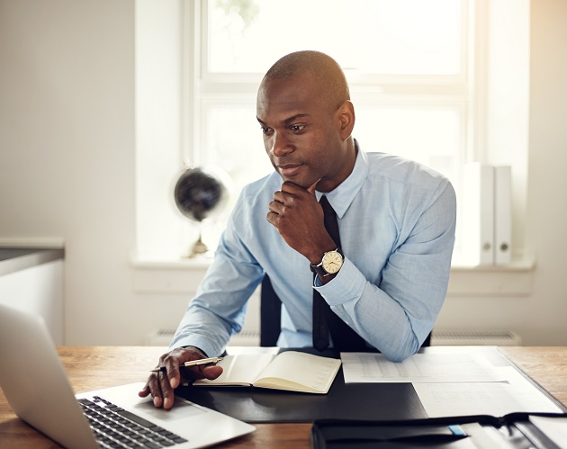 Young African-American financial advisor studies materials on his laptop.