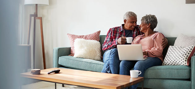 An older African American couple smiles at each other while drinking coffee and looking at a laptop