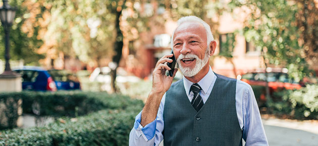 A senior businessman smiles while talking on the phone.