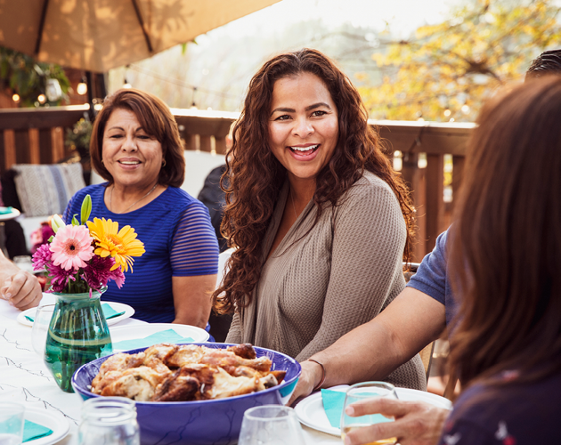 a small group of adult women sitting at outdoor dining table.
