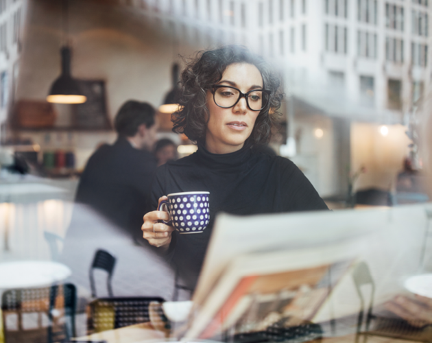 An adult woman drinking coffee while reading papers.