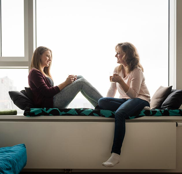 mother and daughter sit and drink coffee together