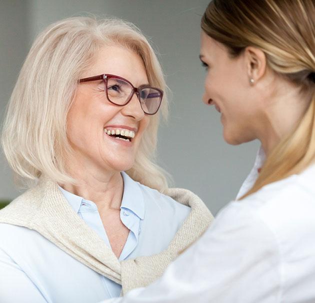 Senior mother smiles at older, grown daughter