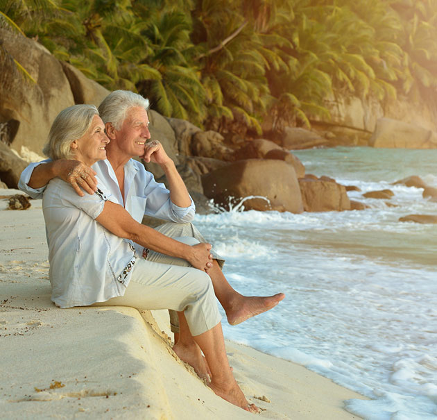 older married couple sits on the beach overlooking the water at sunset