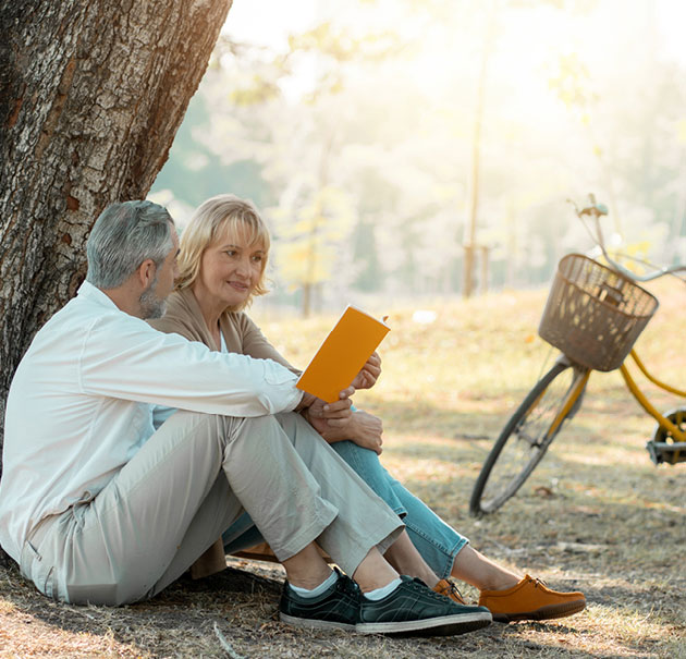 An older man and woman share a book while sitting under a tree