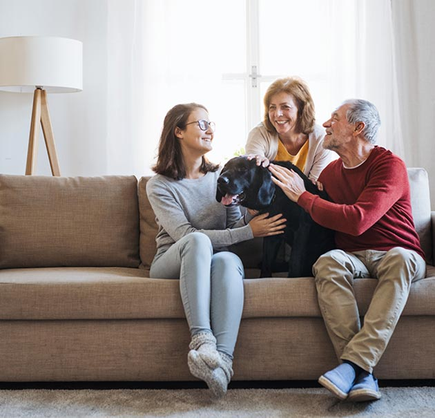 happy family sits on couch petting dog