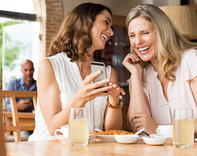 Two middle age women laugh while looking at a phone together