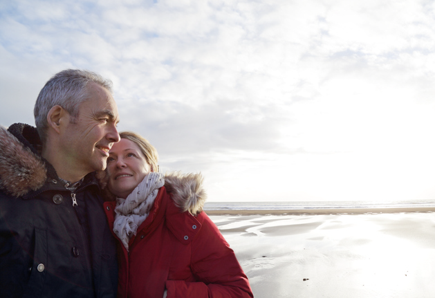 Older couple in winter coats embracing on beach