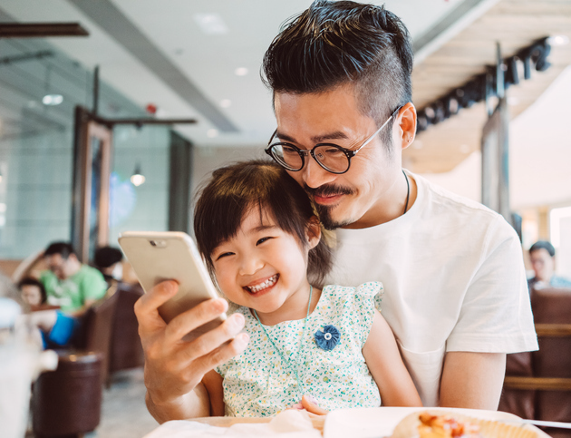Father with daughter in lap laughing at smartphone