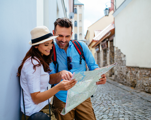 Young couple on vacation looking at a map