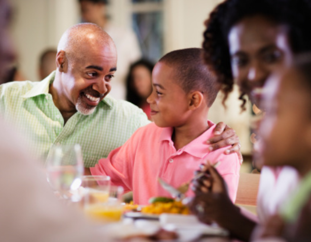 A family smiles while sharing a meal together.