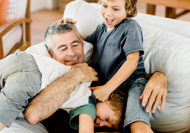 A man plays with his grandchildren.