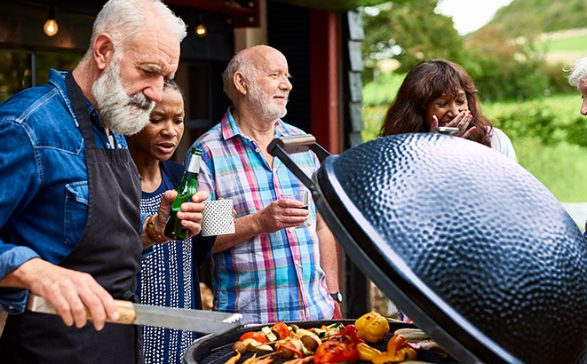 Group of older adults talking around a bbq grill