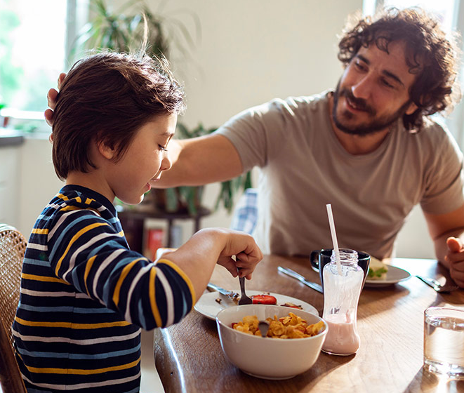 Father and son eating breakfast together