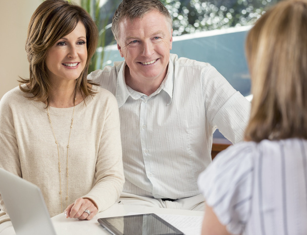 Smiling middle-aged couple sitting at a financial advisor's desk