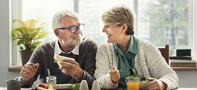 mature couple enjoying a conversation while eating.