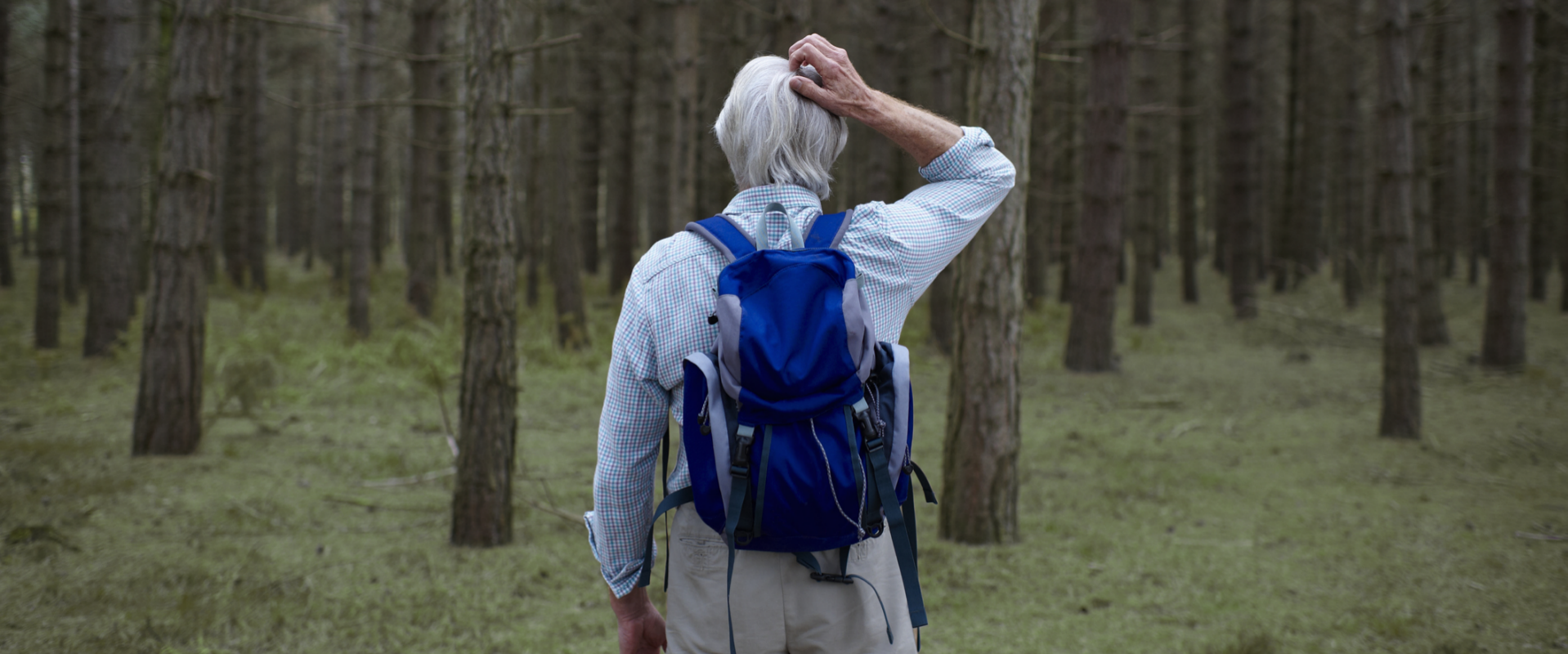 man lost in woods scratching his head