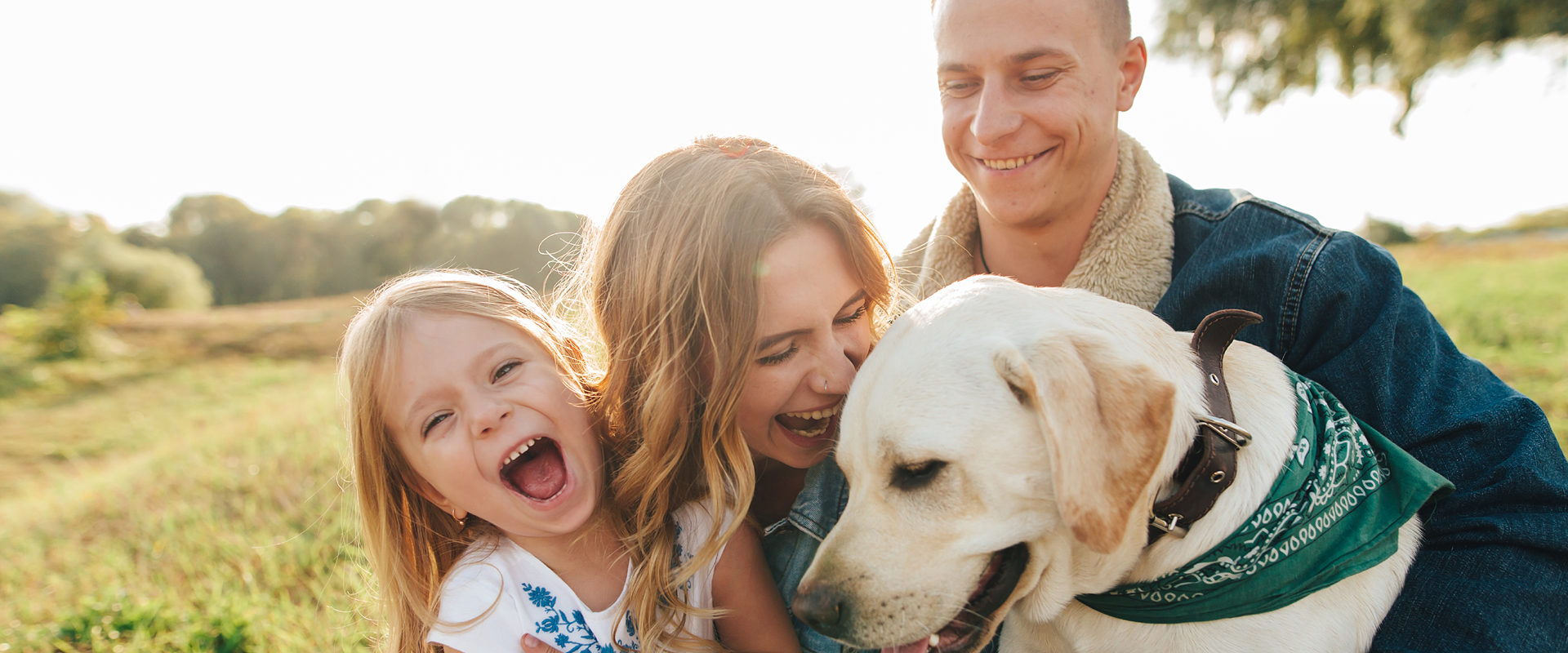 A couple in their thirties with a young girl and dog posing outdoors and laughing