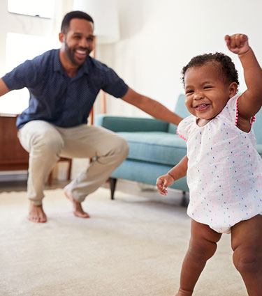 Infant girl taking first steps with dad celebrating in background