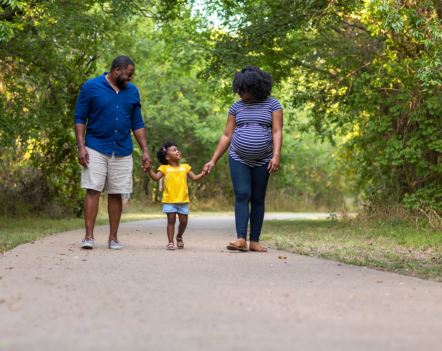 Pregnant woman walking down a trail with husband and young daughter