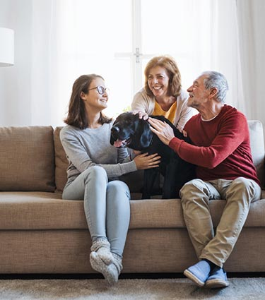 Grandparents sitting on couch with granddaughter and dog