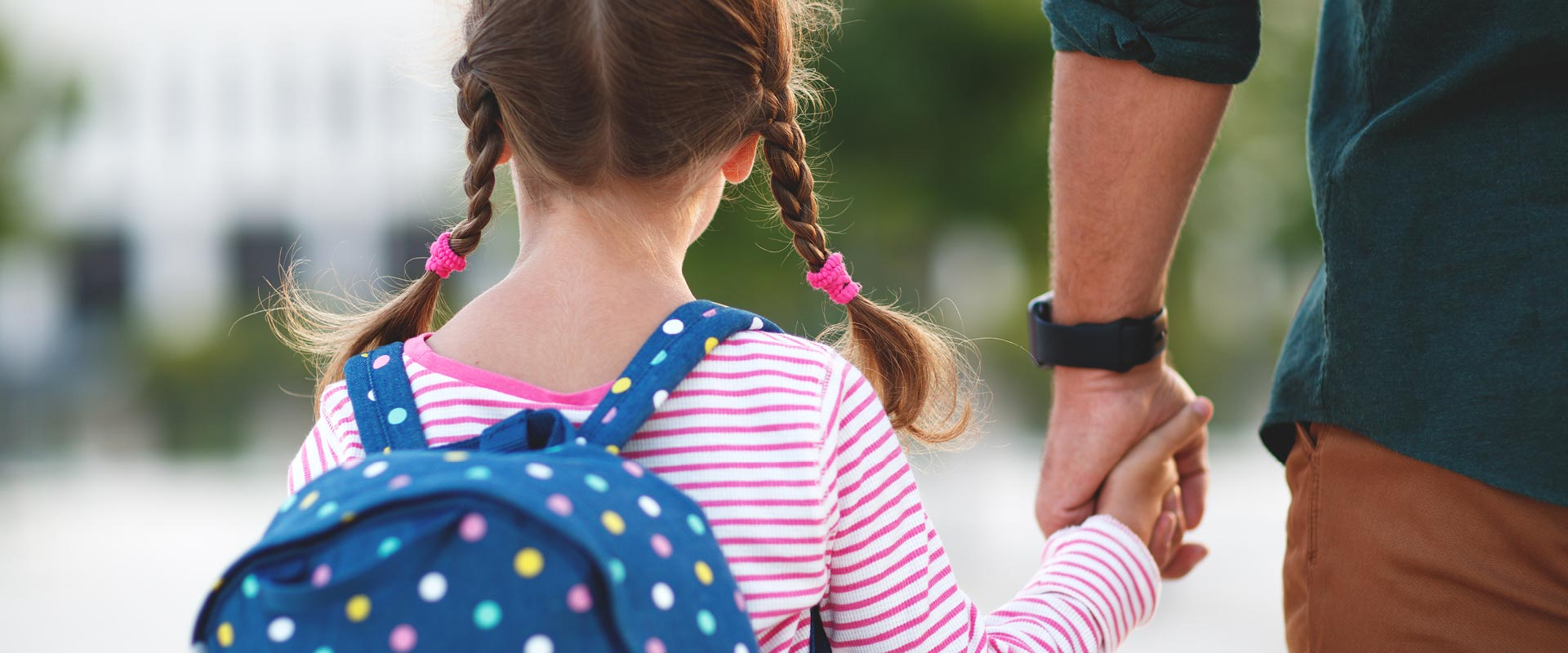 Young girl wearing backpack holding her father's hand
