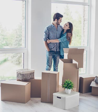 Young couple surrounded by moving boxes in new home