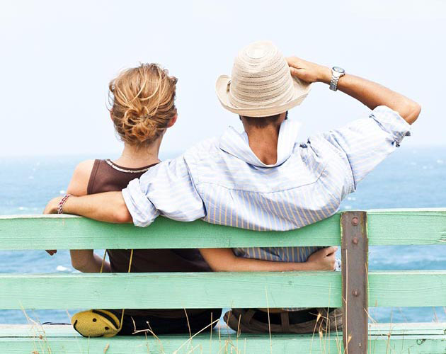 Man and woman sitting on bench overlooking ocean