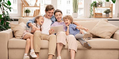 Young family with mom, dad and two kids sitting out the couch reading and laughing together.
