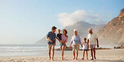 Multi-generational family walking together along the beach.