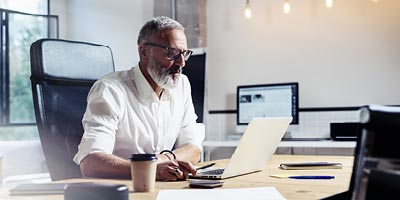 Older man working on computer trying to determine if he can take out a loan on his life insurance policy