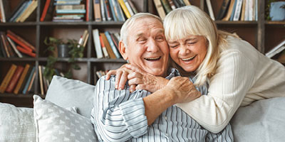 Senior adult couple hugging and smiling.