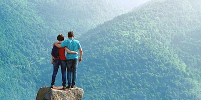 A couple standing on a mountaintop surrounded by a sea of green trees on surrounding mountaintops.