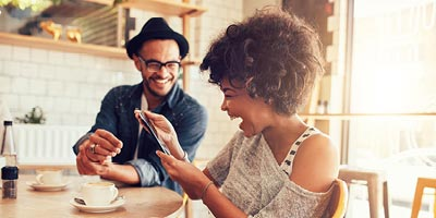 Millennials laughing over coffee, symbolizing a generation that should consider buying life insurance